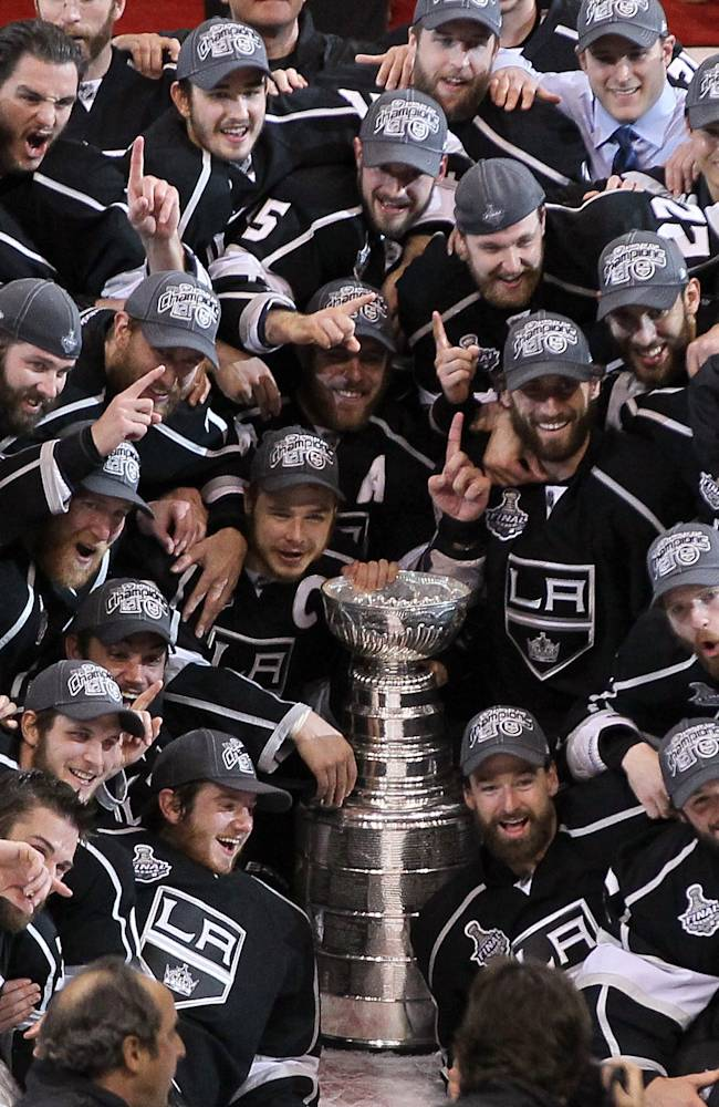 Captain Dustin Brown #23, assistant captain Anze Kopitar #11 and other members of the Los Angeles Kings surround the Stanley Cup during a group photo after the Kings defeated the New Jersey Devils 6-1 to win the Stanley Cup in Game Six of the 2012 Stanley Cup Final at Staples Center on June 11, 2012 in Los Angeles, California. (Photo by Jeff Gross/Getty Images)