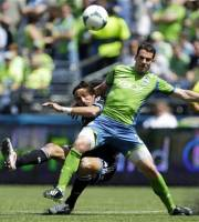 Seattle Sounders' Zach Scott, right, defends as San Jose Earthquakes' Alan Gordon, left, attempts a shot in the first half of an MLS soccer match, Saturday, May 11, 2013, in Seattle. (AP Photo/Ted S. Warren)