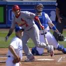 St. Louis Cardinals' Yadier Molina, center, hits an RBI-double as Los Angeles Dodgers starting pitcher Ted Lilly, foreground, and catcher A.J. Ellis look on during the first inning of their baseball game on Saturday, May 25, 2013, in Los Angeles. (AP Photo/Mark J. Terrill)