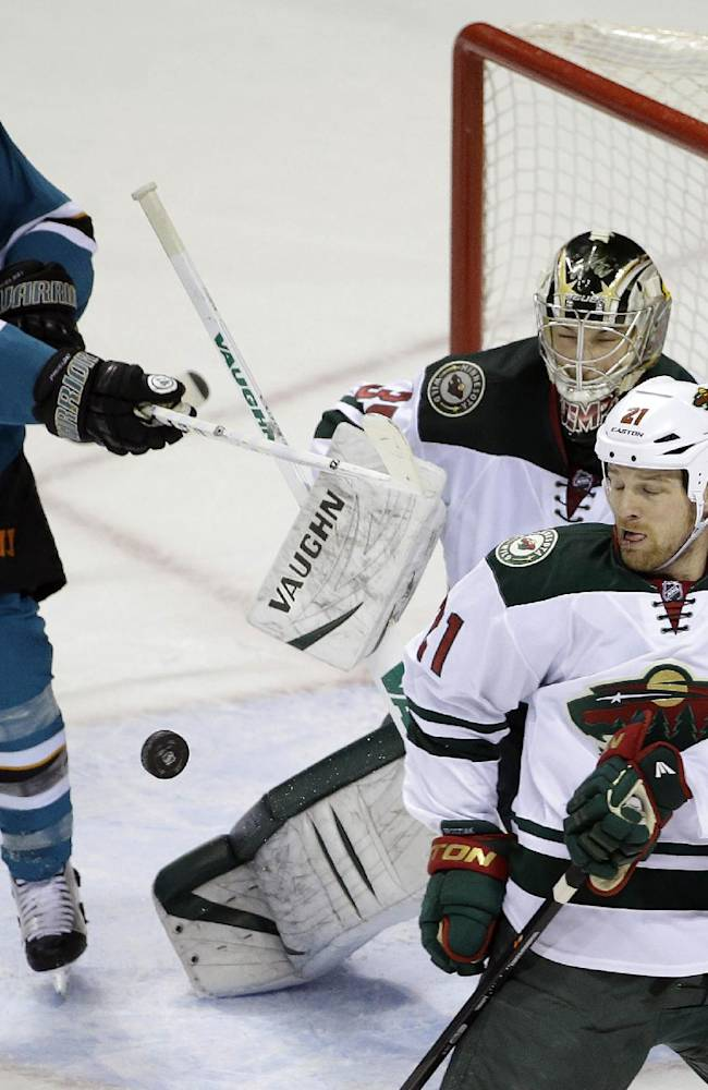 Minnesota Wild goalie Darcy Kuemper, center, stops a shot attempt from San Jose Sharks' Joe Pavelski (8) during the first period of an NHL hockey game on Saturday, Jan. 25, 2014, in San Jose, Calif