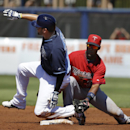 Tampa Bay Rays' David DeJesus, left, reaches second on a double off Minnesota Twins' Ricky Nolasco as Twins shortstop Danny Santana, right, tries to make the play in the first inning of an exhibition baseball game, Sunday, March 2, 2014, in Port Charlotte
