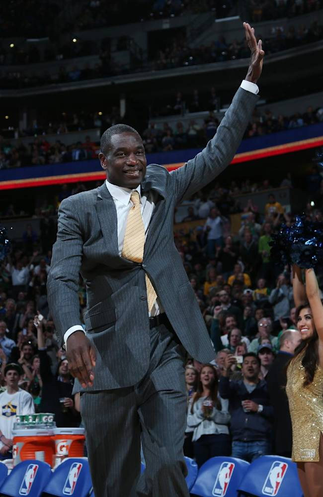 Former Denver Nuggets center Dikembe Mutombo waves to crowd as he is introduced during halftime ceremony to honor the players and coaches on the 1994 Denver team that upset top-seed Seattle SuperSonics in the opening round of the NBA Playoffs on Monday, March 17, 2014, in Denver.  The ceremony was staged during halftime of the Nuggets' 110-100 victory over the Los Angeles Clippers