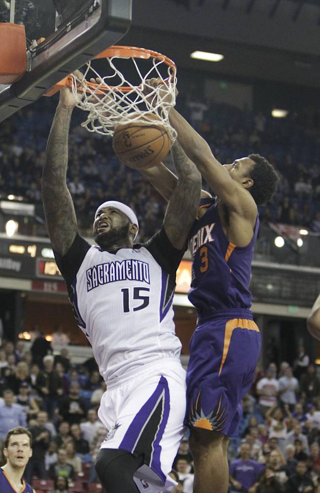 Sacramento Kings center DeMarcus Cousins, left, stuffs against Phoenix Suns guard Ish Smith during the fourth quarter of an NBA basketball game in Sacramento, Calif., Tuesday, Nov. 19, 2013.  The Kings won 107-104
