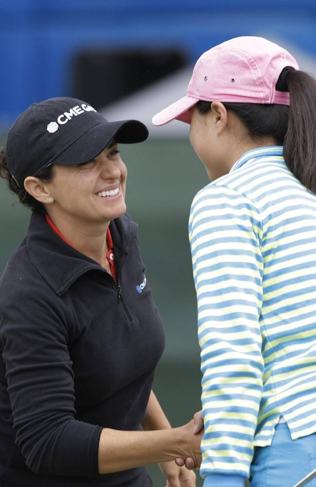 Mo Martin, left, is greeted by Cih-Hui Chen, right, of Taiwan, on the ninth green of the Lake Merced Golf Club after finishing the first round of the Swinging Skirts LPGA Classic golf tournament Thursday, April 24, 2014, in Daly City, Calif. Martin shot a 3-under-par 69