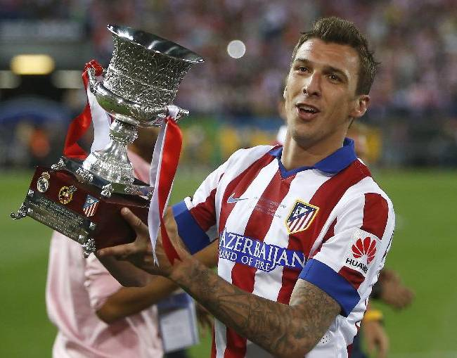 Atletico' Mandzukic celebrates the victory with the trophy during a Spanish Supercup second leg soccer match between Real Madrid and Atletico Madrid at Vicente Calderon stadium in Madrid, Spain, early Saturday, Aug. 23, 2014