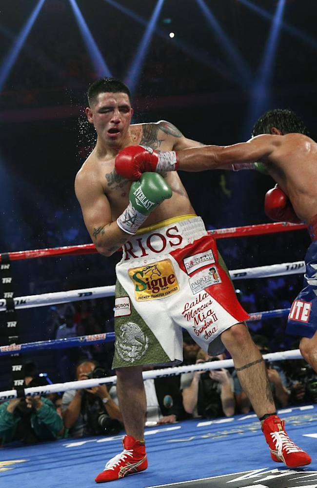 Manny Pacquiao, from the Philippines, right, lands a left to Brandon Rios of the United States during their WBO international welterweight title fight Sunday, Nov. 24, 2013, in Macau. Pacquiao defeated Rios by unanimous decision on Sunday to take the WBO international welterweight title and return to his accustomed winning ways after successive defeats