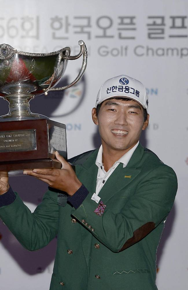 In this photo released by OneAsia, South Korea's Kang Soon-hoon poses with his trophy for photographers after winning the Korea Open golf tournament at Woo Jeong Hills Country Club near Cheonan, South Korea, Sunday, Oct. 20, 2013