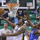 Utah Jazz's Derrick Favors, left, lays the ball up as Dallas Mavericks' Samuel Dalembert (1) defends during the first quarter of an NBA basketball game Tuesday, April 8, 2014, in Salt Lake City The Associated Press