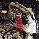 Miami Heat's Dwyane Wade (3) is pressured by San Antonio Spurs' Tim Duncan (21) during the second half of Game 3 in their NBA Finals basketball series, Tuesday, June 11, 2013, in San Antonio. (AP Photo/Eric Gay)