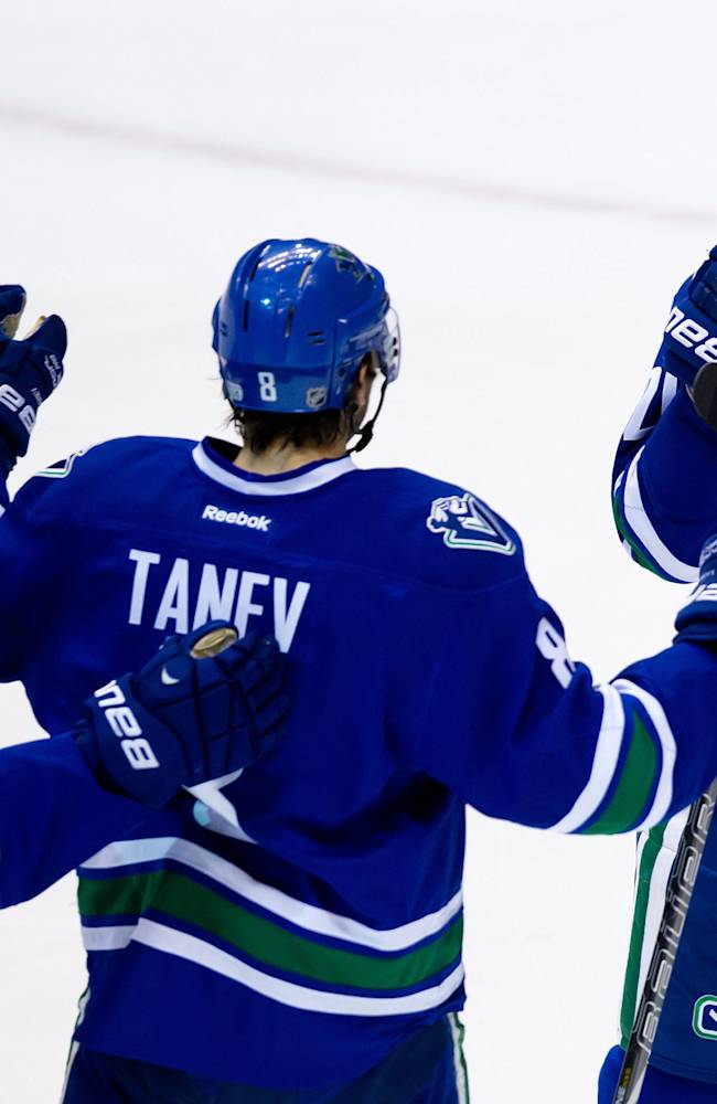 Vancouver Canucks' Dale Weise, from left to right, Chris Tanev and Chris Higgins celebrate Higgins' goal against the Nashville Predators during second period NHL hockey action in Vancouver, British Columbia on Thursday Jan, 23, 2014