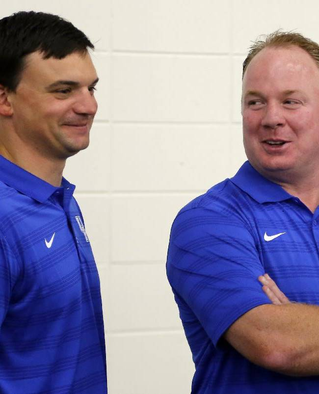 Kentucky head coach Mark Stoops, right and offensive coordinator Neal Brown share a laugh during the team's NCAA college football media day, Friday, Aug. 8, 2014, in Lexington, Ky