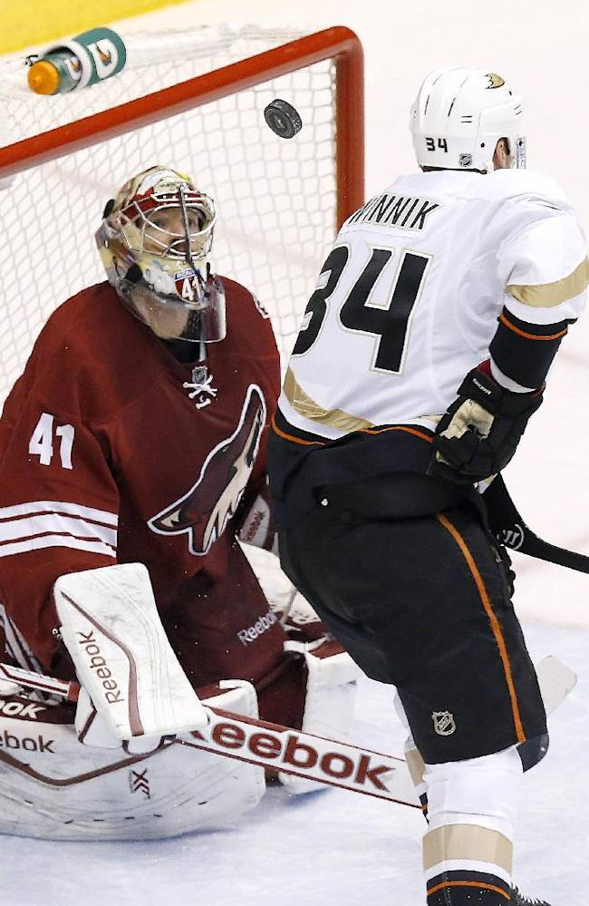 Phoenix Coyotes' Mike Smith (41) looks at the puck in the air as Anaheim Ducks' Daniel Winnik (34) tries to redirect the shot during the first period of an NHL hockey game Saturday, Nov. 23, 2013, in Glendale, Ariz