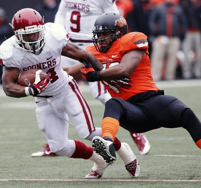 Oklahoma running back Brennan Clay, left, is tackled by Oklahoma State linebacker Ryan Simmons in the second quarter of an NCAA college football game in Stillwater, Okla., Saturday, Dec. 7, 2013. Oklahoma won 33-24