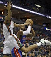 Detroit Pistons' Greg Monroe(10) puts up a shot against Milwaukee Bucks' John Henson, left, during the first half of an NBA basketball game Wednesday, Jan. 22, 2014, in Milwaukee. (AP Photo/Jeffrey Phelps)