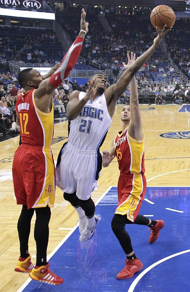 Orlando Magic's Maurice Harkless (21) gets off a shot as he gets between Houston Rockets' Dwight Howard (12) and Chandler Parsons, right, during the first half of an NBA basketball game in Orlando, Fla., Wednesday, March 5, 2014