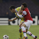Napoli midfielder Christian Maggio, left, and Arsenal's Santi Cazorla fight for the ball during a Champions League, group F soccer match, at the Naples San Paolo stadium, Italy, Wednesday, Dec. 11, 2013