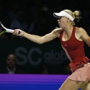 Caroline Wozniacki of Denmark hits a return to Serena Williams of the U.S. during their WTA Finals singles semi-final tennis match at the Singapore Indoor Stadium October 25, 2014. REUTERS/Edgar Su