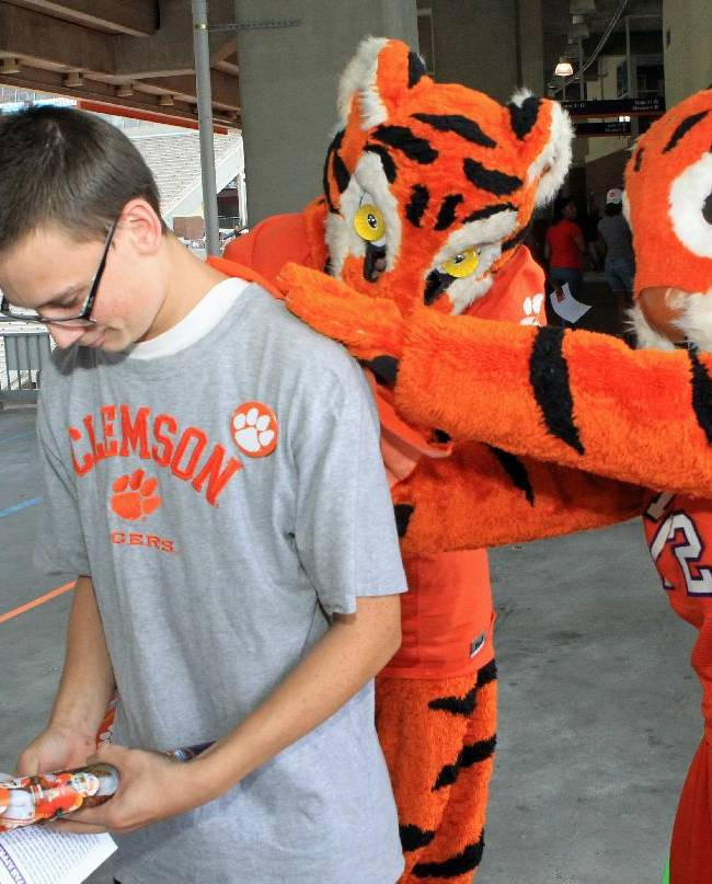 Clemson NCAA college football Tiger mascots autograph a fan's t-shirt during Fan Appreciation Day at Memorial Stadium in Clemson, S.C. on Sunday, Aug, 17, 2014