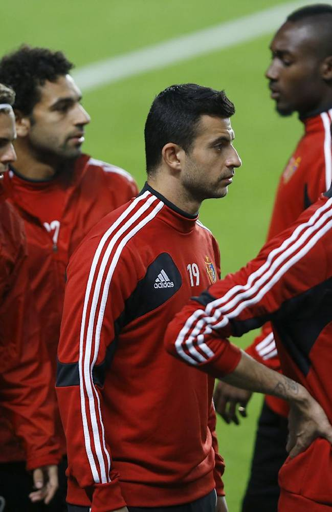 Basel's Behrang Safari, centre, waits with teammates to warm up during a training session at Stamford Bridge Stadium in London, Tuesday, Sept. 17, 2013. Chelsea will play FC Basel in a Champions League match at Stamford Bridge on Wednesday