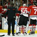 Chicago Blackhawks goalie Corey Crawford (50) is helped off the ice after suffering an injury during the first period of an NHL hockey game against the Florida Panthers on Sunday, Dec. 8, 2013, in Chicago, Ill. (AP Photo/Andrew A. Nelles)