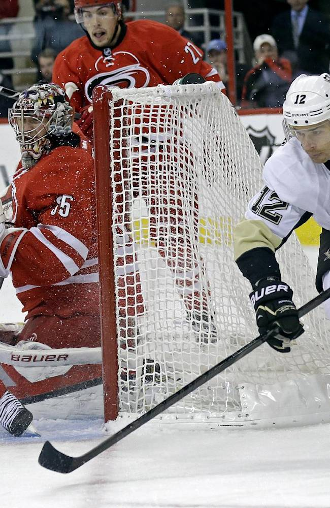 Pittsburgh Penguins' Chuck Kobasew (12) and Carolina Hurricanes' Jay Harrison (44) reach for the puck as Hurricanes goalie Justin Peters (35) defends the goal during the first period of an NHL hockey game in Raleigh, N.C., Monday, Oct. 28, 2013