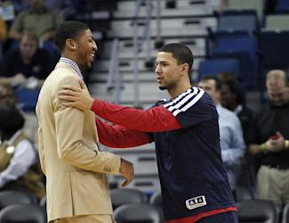 New Orleans Pelicans shooting guard Austin Rivers, right, laughs with power forward Anthony Davis before an NBA basketball game against the Dallas Mavericks in New Orleans, Wednesday, Dec. 4, 2013. Davis is out for four to six weeks for a hand injury he sustained in a recent game against the Chicago Bulls. (AP Photo/Gerald Herbert)
