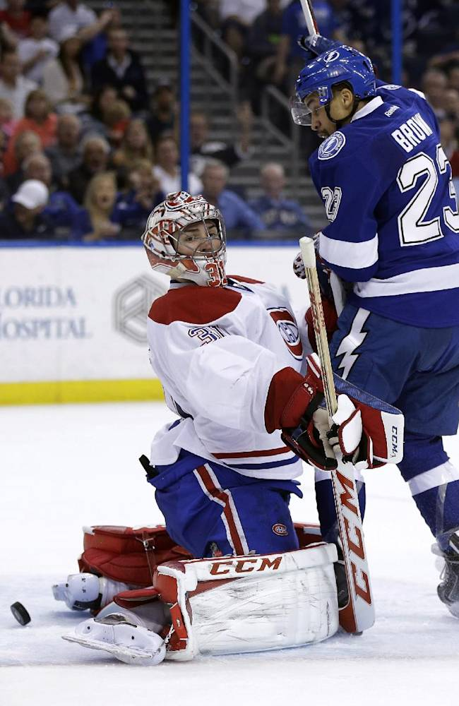 Tampa Bay Lightning right wing J.T. Brown (23) makes contact with Montreal Canadiens goalie Carey Price (31), nullifying a goal by Tampa Bay's Teddy Purcell during the second period of an NHL hockey game Tuesday, April 1, 2014, in Tampa, Fla