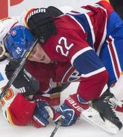 Montreal Canadiens' Dale Weise (22) is brought down by Calgary Flames' Kevin Westgarth (15) during the first period of an NHL hockey game Tuesday, Feb. 4, 2014, in Montreal. (AP Photo/The Canadian Press, Graham Hughes)