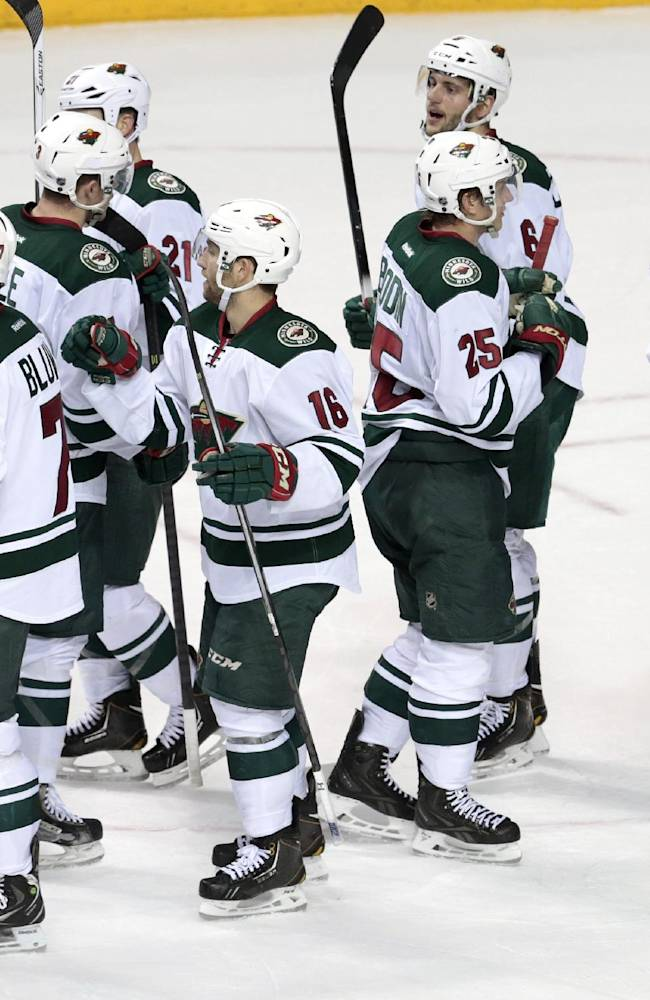 The Minnesota Wild celebrate after shutting out the Nashville Predators 4-0 in an NHL hockey game Sunday, Jan. 12, 2014, in Nashville, Tenn