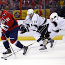 Washington Capitals defenseman Dmitry Orlov (81), from Russia, skates with the puck as he is pursued by Los Angeles Kings left wing Dwight King (74) and center Jarret Stoll (28) in the second period of an NHL hockey game, Tuesday, March 25, 2014, in Washi