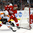 Detroit Red Wings goalie Jimmy Howard (35) stops a Philadelphia Flyers right wing Jakub Voracek (93), of the Czech Republic, shot as Red Wings defenseman Niklas Kronwall (55), of Sweden, applies pressure in the first period of an NHL hockey game in Detr