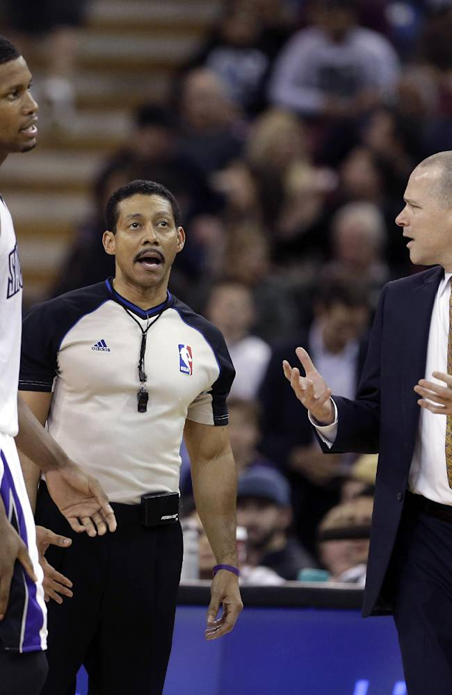 Sacramento Kings head coach Michael Malone, right, questions official Bill Kennedy about the foul he called on Kings forward Rudy Gay, left, during the fourth quarter of an NBA basketball game against the  New Orleans Pelicans in Sacramento, Calif., Monday, March 3, 2014.  The Kings won 96-89