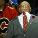 An usher, right, with a face painted on the back of his head, wears his uniform backward as a Halloween costume while he works at the Nashville Predators-Calgary Flames NHL hockey game in Calgary, Alberta, Friday, Oct. 31, 2014 The Associated Press