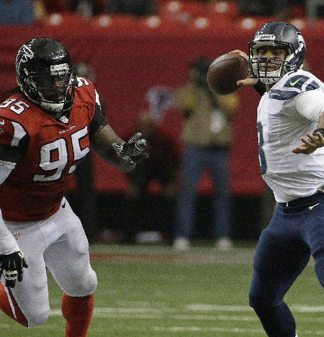 Seattle Seahawks quarterback Russell Wilson (3) works as Atlanta Falcons defensive tackle Jonathan Babineaux (95) pursues during the first half of an NFL football game, Sunday, Nov. 10, 2013, in Atlanta