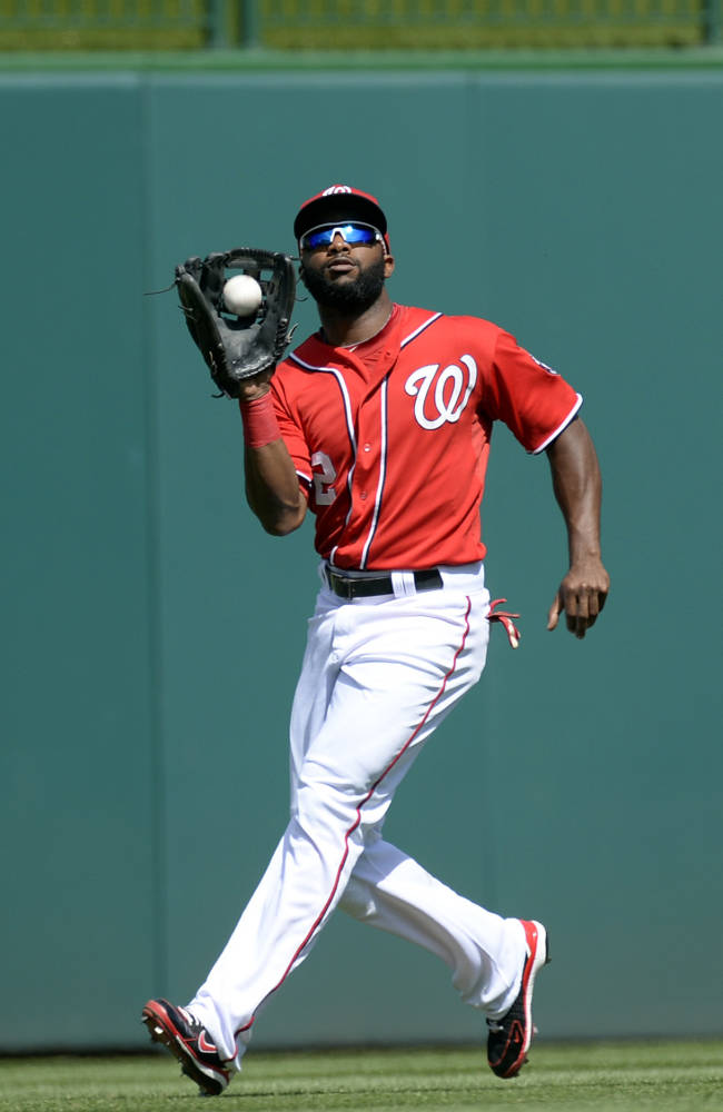 Washington Nationals center fielder Denard Span catches a fly ball hit by Philadelphia Phillies' Jimmy Rollins during the first inning of their baseball game at Nationals Park in Washington, Sunday, Sept. 15, 2013