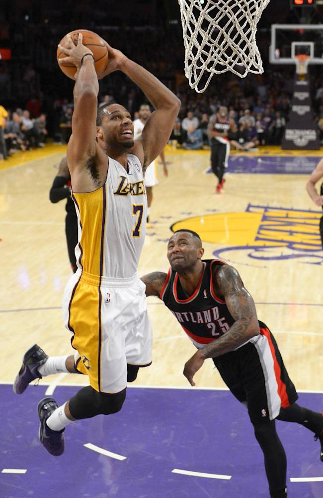 Los Angeles Lakers forward Xavier Henry, left, goes up for a dunk as Portland Trail Blazers guard Mo Williams defends during the second half of an NBA basketball game, Sunday, Dec. 1, 2013, in Los Angeles