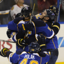 St. Louis Blues' Barret Jackman (5) is congratulated by teammates Adam Cracknell, right, and Roman Polak (46), of the Czech Republic, after his game-winning goal against the Chicago Blackhawks during overtime in Game 2 of a first-round NHL hockey playoff series, Saturday, April 19, 2014, in St. Louis. (AP Photo/Bill Boyce)