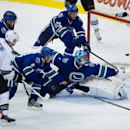 San Jose Sharks' Joe Pavelski, from left to right, and Vancouver Canucks' Mike Santorelli, Chris Tanev, Alexander Edler, of Sweden, watch as goalie Roberto Luongo allows the game-tying goal to Sharks' Tomas Hertl, of the Czech Republic, during third perio