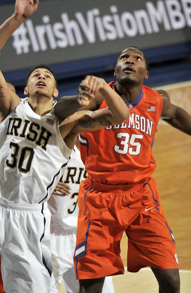 Notre Dame forward Zach Auguste, left, and Clemson center Landry Knoko reach for a rebound in first half of an NCAA college basketball game, Tuesday, Feb. 11, 2014, in South Bend, Ind