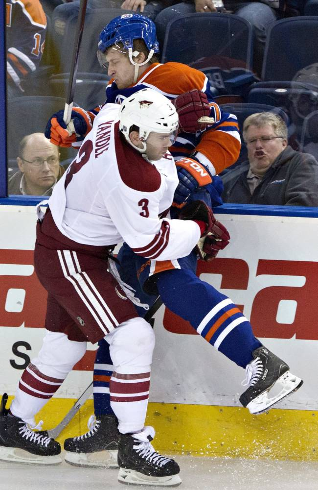 Phoenix Coyotes' Keith Yandle (3) checks Edmonton Oilers' Anton Belov (77) during third period NHL hockey action on Friday Jan. 24, 2014, in Edmonton, Alberta