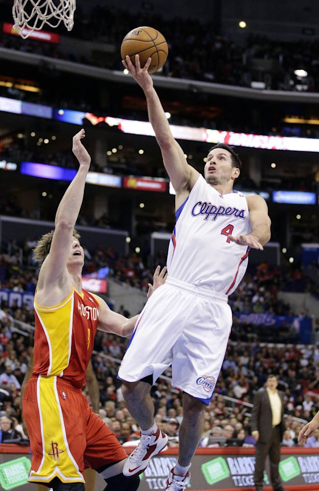 Los Angeles Clippers' J.J. Redick puts up a shot as Houston Rockets' Omer Asik, left, of Turkey, watches during the first half of an NBA basketball game on Monday, Nov. 4, 2013, in Los Angeles. The Clippers won 137-118