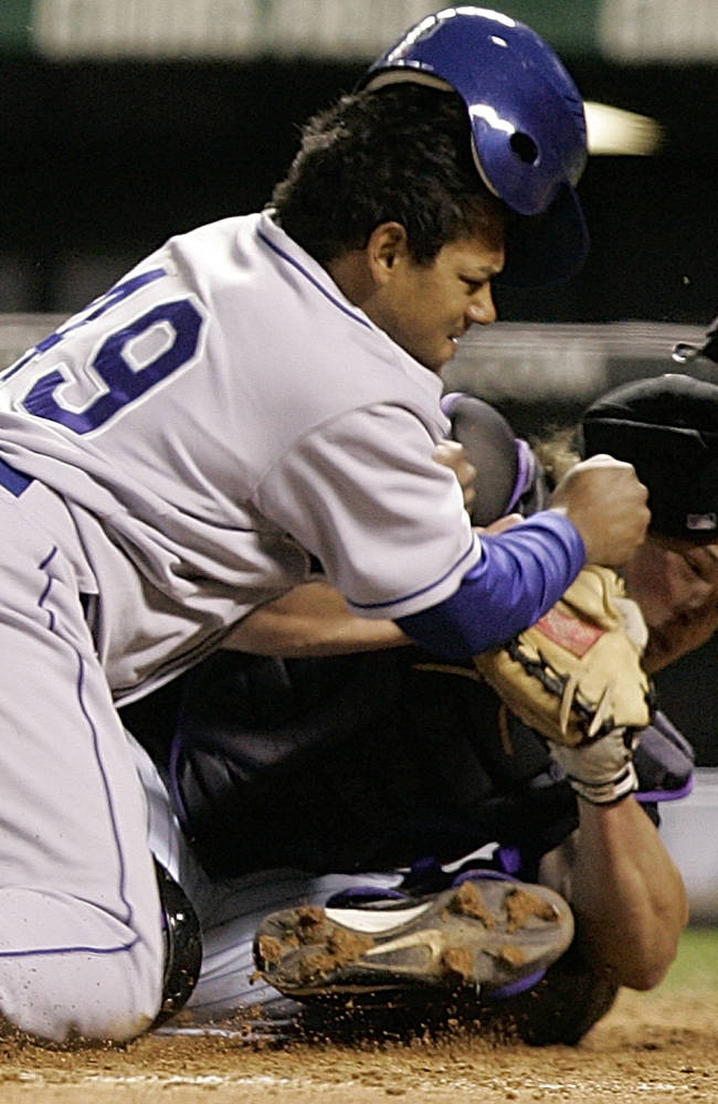 In this Sept. 27, 2006, file photo, Los Angeles Dodgers' Delwyn Young, left, is out at home plate as he collides with Colorado Rockies catcher JD Closser during the seventh inning of a baseball game in Denver. New York Mets general manager Sandy Alderson, chairman of the rules committee, announced Wednesday, Dec. 11, 2013, that Major League Baseball plans to eliminate home plate collisions. He said player health and increased awareness of concussions were behind the decision