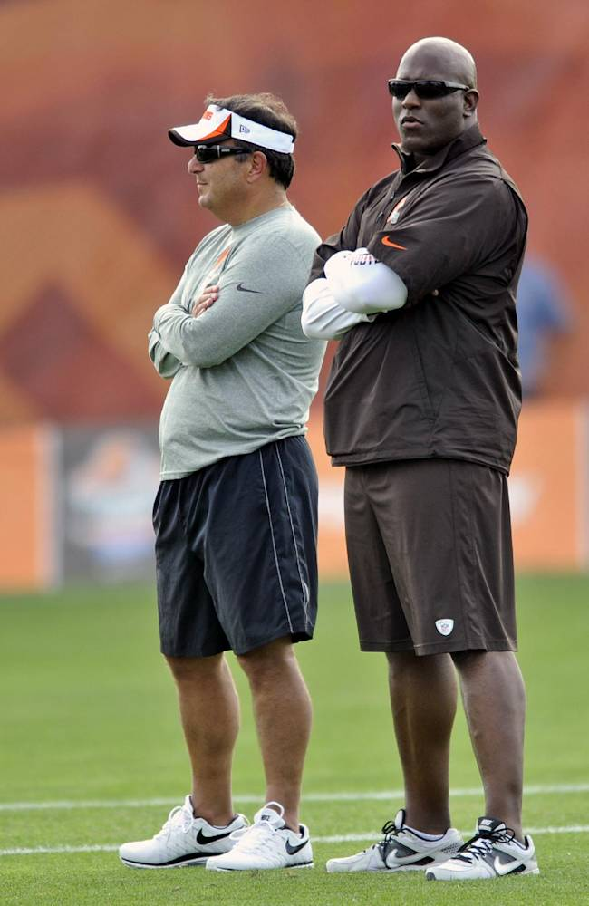 In this July 31, 2013, file photo, Cleveland Browns general manager Mike Lombardi, left, and assistant general manager Ray Farmer stand on the field during training camp at the NFL football team's facility in Berea, Ohio. The Browns fired their coach after one season. Now they're sweeping out their front office. Owner Jimmy Haslam announced Tuesday, Feb. 11, 2014,  that CEO Joe Banner will step down in the next two months and general manager Michael Lombardi is leaving the team. Haslam also said assistant GM Ray Farmer, who was pursued by Miami to be the Dolphins' GM this winter, has been promoted and will immediately take the over the team's football operations and lead the Browns during free agency and draft