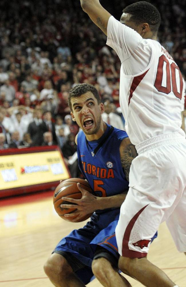 Florida guard Scottie Wilbekin (5) eyes the basket while being guarded by Arkansas guard Rashad Madden (00) during an NCAA college basketball game in Fayetteville, Ark., Saturday, Jan. 11, 2014