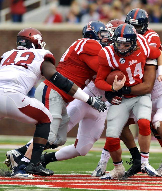 Mississippi quarterback Bo Wallace (14) is wrapped up by an Arkansas defender with Arkansas defensive end Chris Smith (42) going in to tackle during the first half of an NCAA college football game on Saturday, Nov. 9, 2013, in Oxford, Miss. Mississippi won 34-24