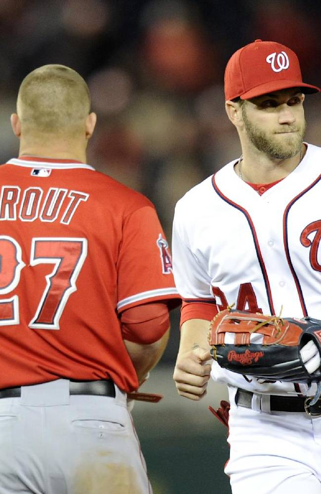 Washington Nationals left fielder Bryce Harper (34) runs from the field past Los Angeles Angels' Mike Trout (27) during the middle of the seventh inning of a baseball game, Monday, April 21, 2014, in Washington. The Angels won 4-2