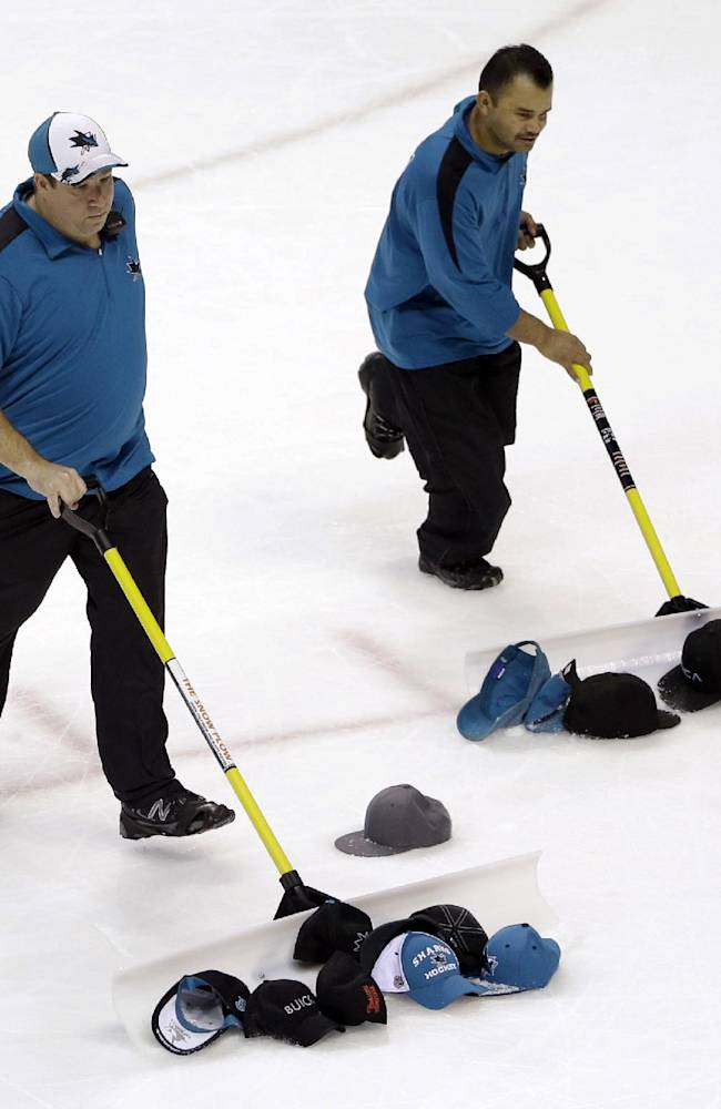 Workers gather hats thrown onto the ice by fans after San Jose Sharks' Martin Havlat's third goal of the NHL hockey game against the Colorado Avalanche, during the third period Friday, April 11, 2014, in San Jose, Calif. San Jose won 5-1