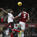 Fulham s Darren Bent, left, and West Ham United s James Tomkins, right, fight for the ball, during their English Premier League soccer match in London, Saturday, Nov. 30, 2013