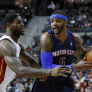 Miami Heat small forward LeBron James, left, defends Detroit Pistons small forward Josh Smith (6) in the second quarter of an NBA basketball game in Auburn Hills, Mich., Sunday, Dec. 8, 2013. (AP Photo/Paul Sancya)