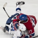 Tampa Bay Lightning's Ondrej Palat and Montreal Canadiens' Tom Gilbert crash to the ice during the first period of an NHL hockey game Tuesday, Jan. 6, 2015, in Montreal The Associated Press